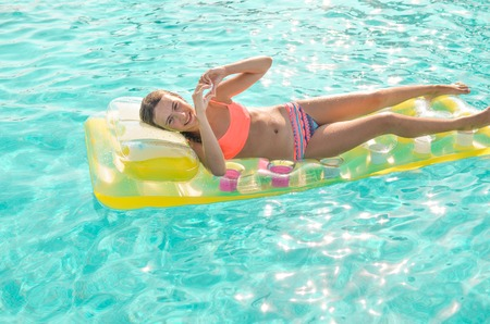 Smiling teen girl floating in the turquoise pool in bright coral bikini on a yellow mattress. Girl shows heart symbol. Summer holidays, fun summertime and watersports concept.
