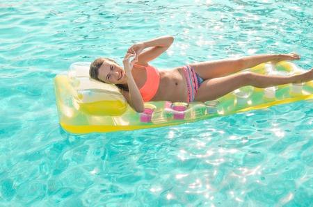 Une adolescente souriante flottant dans la piscine turquoise en bikini corail brillant sur un matelas jaune. La fille montre le symbole du coeur. Vacances d'été, été amusant et concept de sports nautiques.