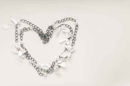 Top view of heart made of silver chain necklace in black and white colors. Valentine's Day, love, wedding or romance concept.