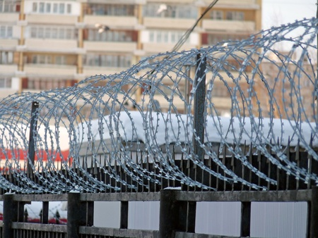 Fence topped with barbed wire on the background of an apartment house  photo