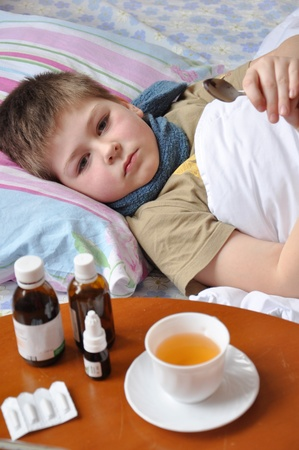 Sick boy lying in bed. Drugs on the table