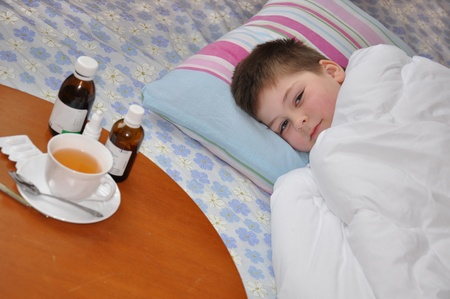 enfant malade: Sick boy gisant au lit. M�dicaments sur la table.