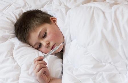 Sick boy looks at the thermometer. Bed rest