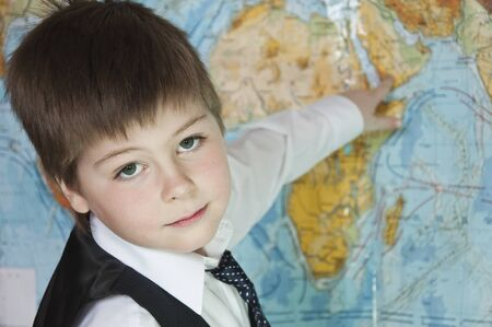 nine years old: The boy is studying the physical map of the world
