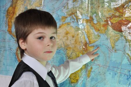 7 8: The boy is studying the physical map of the world