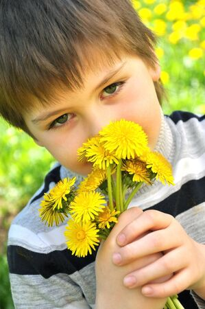 A boy with a bouquet of dandelions photo