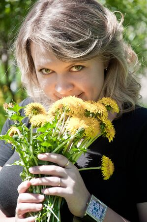 Portrait of a young girl on the lawn with a bouquet of dandelions photo