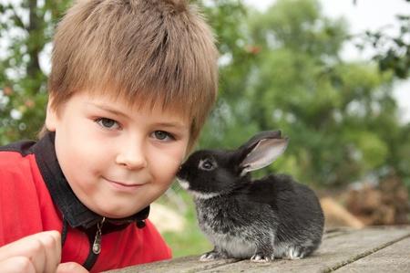 コテージ、ガーデンの中にウサギを持つ少年 写真素材 - 10086890