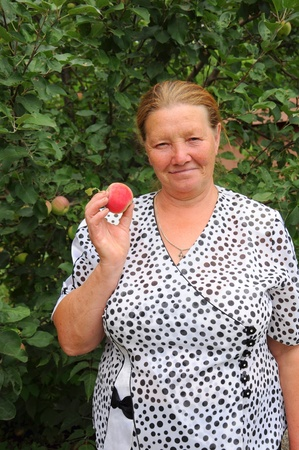 Pensioner in the garden with a red apple in her hand photo