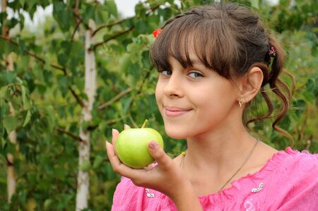 The girl with green apple on the background of birch Stock Photo - 10143033