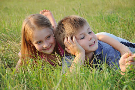 lie forward: Boy and girl resting in a meadow Stock Photo