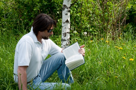 A man reads a book in the park 写真素材
