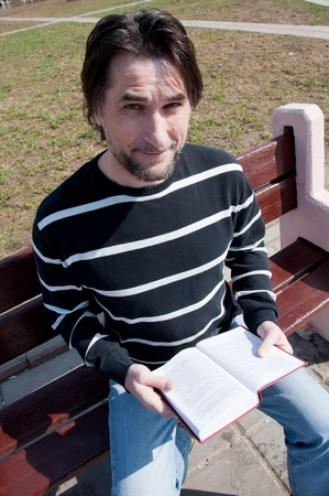 Man with book sitting on a bench photo