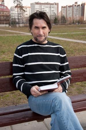 hombre con barba: El hombre con el libro sentado en un banco