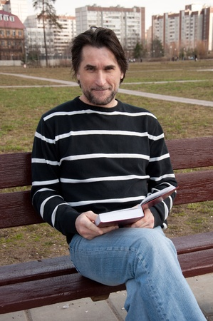 40 years old: Man with book sitting on a bench Stock Photo