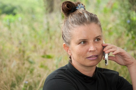 Middle-aged woman talking on cell phone photo
