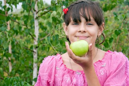 The girl with green apple on the background of birch Stock Photo - 10570171
