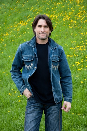 40 years old: The dark-haired man in jeans on a meadow