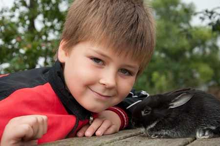 A boy with a rabbit in the garden on a summer residence