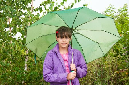 10 to 12 years: Girl with a green umbrella in the park