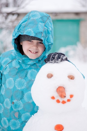 A boy and a snowman - a winter holiday photo