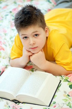 A boy reads a book in bed