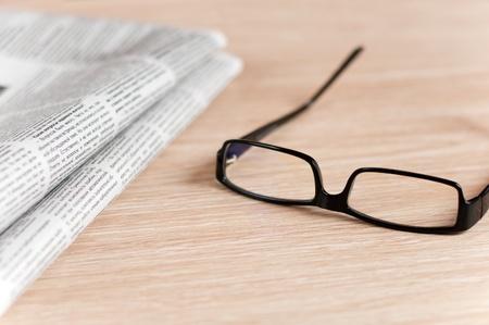 Eyeglasses lying around newspapers photo