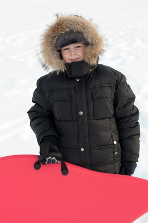 fur hood: Portrait of a boy with a sledge