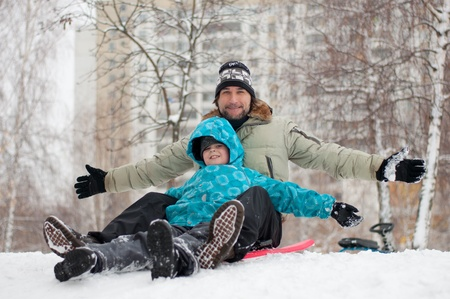 Dad and son riding a frozen hill Stock Photo - 12535824