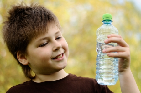 A boy with a bottle of water in nature photo