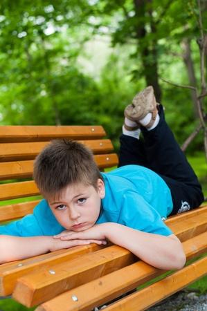 sad boy: The boy lay on a bench