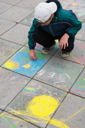 A boy paints chalk on the pavement photo