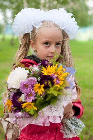 Schoolgirl dressed with a bouquet photo