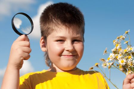 Boy sees flowers through magnifying glass photo