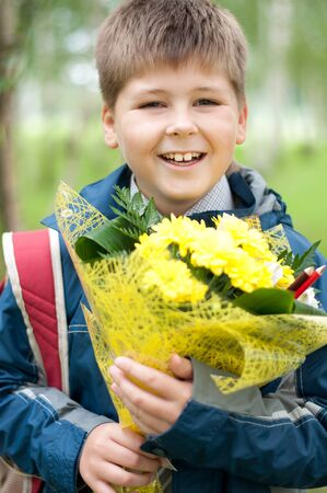 Schoolboy with a bouquet of yellow chrysanthemums in the park photo