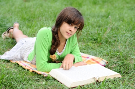 Girl reading a book lying on the grass photo