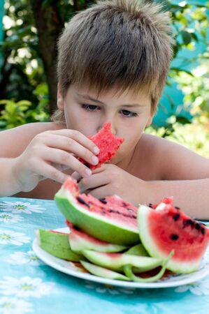 Ragazzo che mangia un cocomero maturo