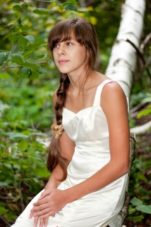 long day: Russian girl in a white dress in a birch forest