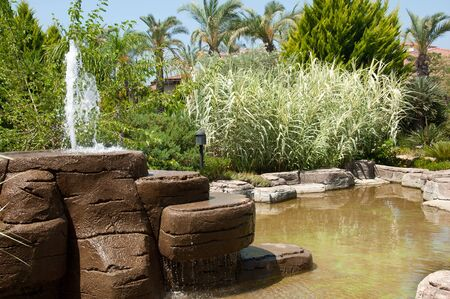 Landscaping - a stone fountain and pond photo