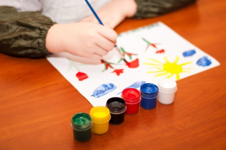 Child draws a picture paints photo