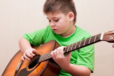 A boy learns to play the guitar photo