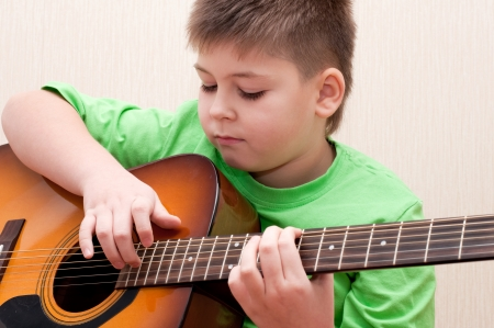 A boy learns to play the guitar