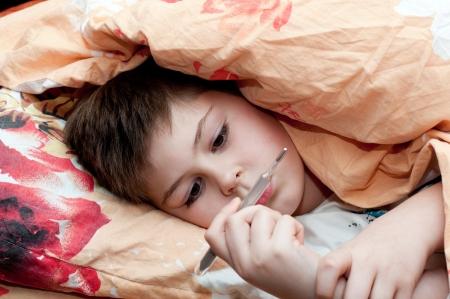 Sick boy lying in bed photo