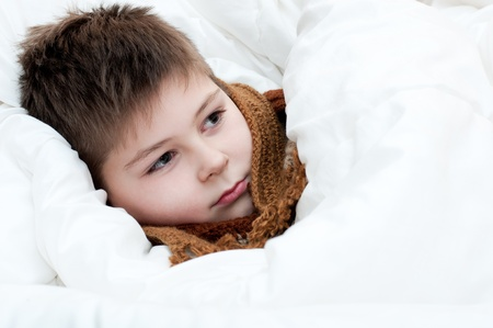 Sick boy lying in bed