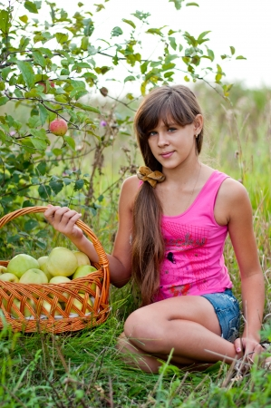 Teen girl with a basket of apples photo