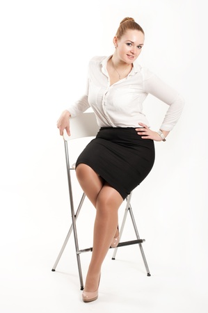 skirt suit: Business woman sitting on a high chair Stock Photo