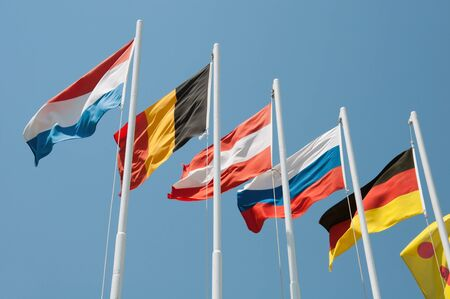 Flags of different countries on a background of blue sky photo