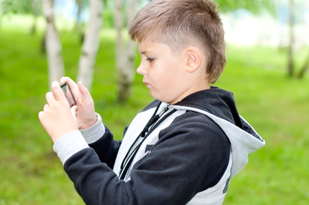 A boy plays on a mobile phone in a park
