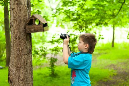 naturalist: Boy photographing a bird feeder