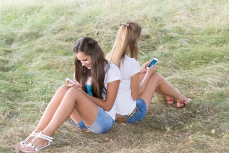 Two teenage girls with cell phones are sitting on the grass